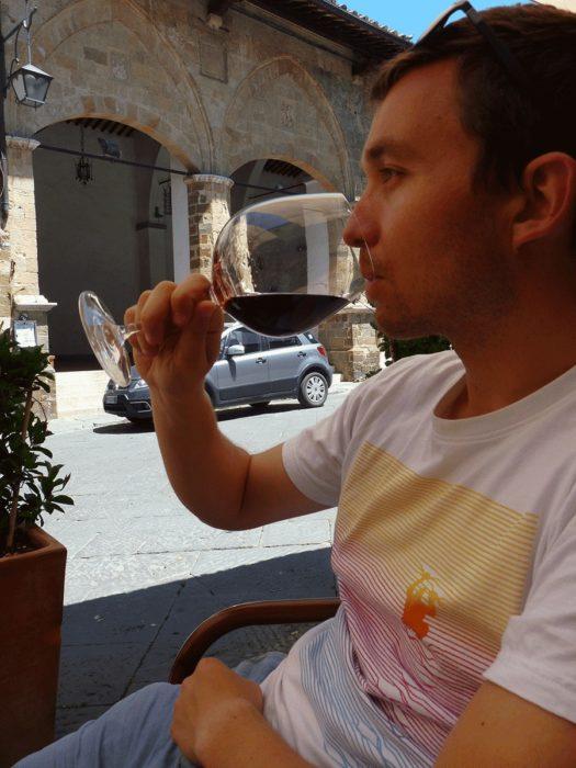 romain boit un verre de vin en toscane